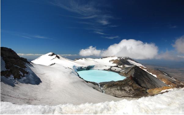 Descrição da imagem: Em um dos cumes da montanha Tongariro, fica o lago de mesmo nome. Dependendo da temperatura, os microrganismos que vivem no lago proporcionam um espetáculo de cores que pode ser azul bem claro (como na imagem descrita) ou em tons de verde esmeralda. O lago é cercado por montes de neve, e o céu está bem claro.